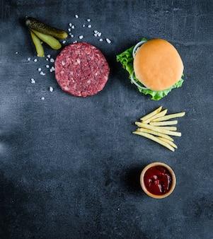 Czerwonego hamburgeru mięsny zbliżenie na czarnym tle