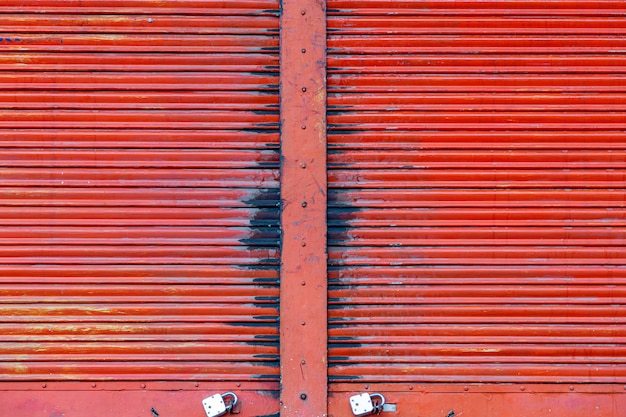 Czerwonego koloru żaluzi drzwi toczny stalowy tło.