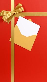 Czerwonego tła prezenta bożego narodzenia złocisty tasiemkowy łęk z pustym zaproszenia lub kartka z pozdrowieniami pionowo