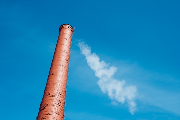 Czerwonej cegły komin z dymem na niebieskim niebie