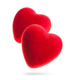 Czerwoni aksamitni serca odizolowywający na bielu.