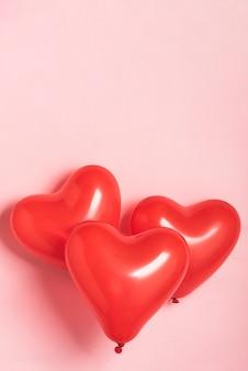 Czerwoni balony na różowym tle z kopii przestrzenią