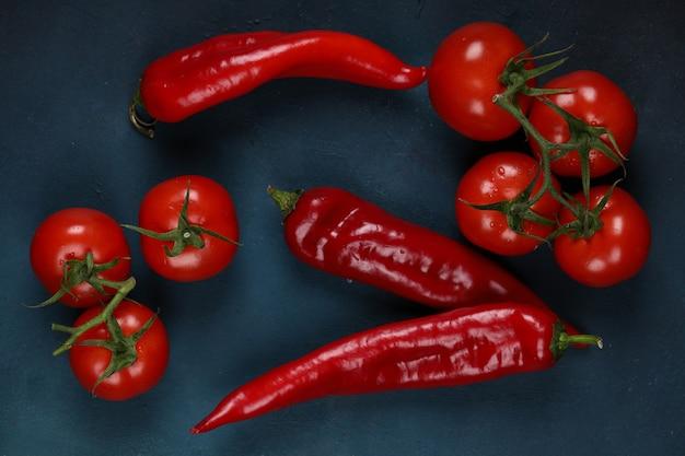 Czerwoni chilli i pomidory na błękitnym tle