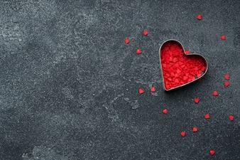 Czerwoni cukrowi serca na ciemnym tle.