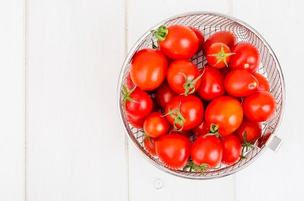Czerwoni dojrzali czereśniowi pomidory na drewnianym stole.