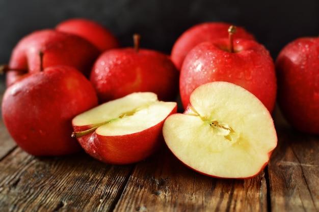 Czerwoni dojrzali jabłka na ciemnej drewnianej powierzchni. pyszne zdrowe owoce. jabłko dabinett