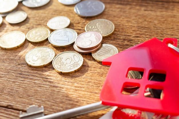 Czerwoni domowi klucze i monety na drewnianym