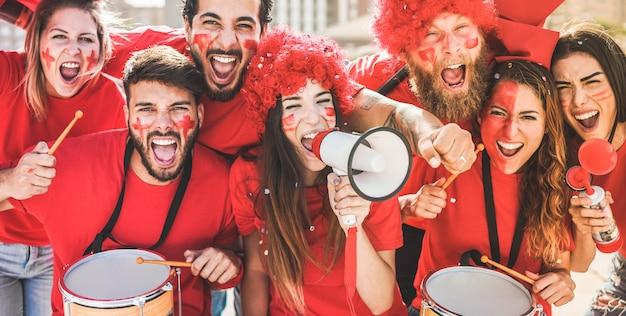 Czerwoni fani sportu krzyczą, jednocześnie wspierając swoją drużynę ze stadionu