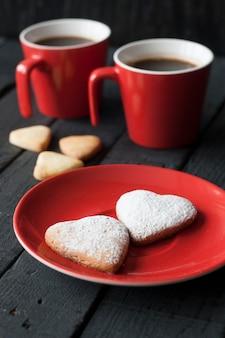 Czerwoni filiżanek i ciastka serca na czarnej powierzchni