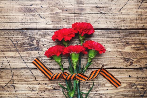 Czerwoni goździki i st. george faborek na drewnianym tle.