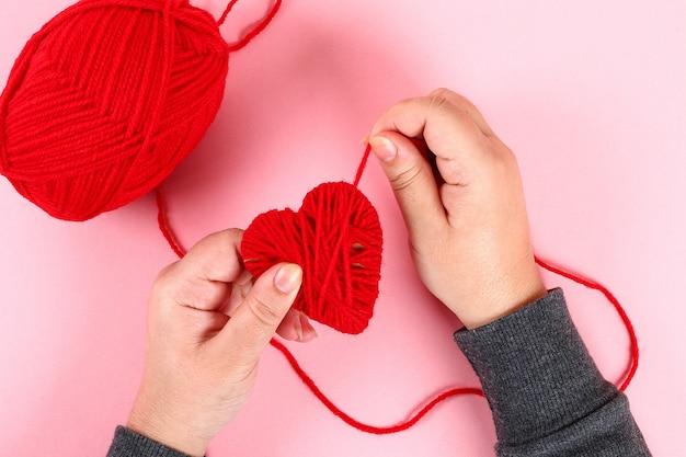 Czerwoni handmade diy serca robić karton, przędza na różowym tle.