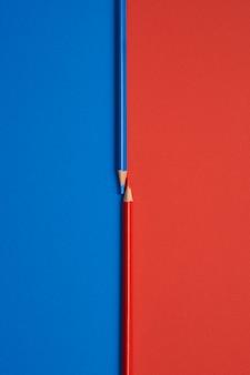 Czerwoni i błękitni barwioni ołówki odizolowywający na stole błękitnym i czerwonym