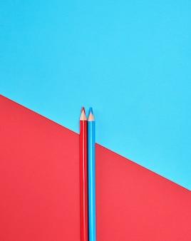 Czerwoni i błękitni drewniani ołówki na koloru abstrakta tle