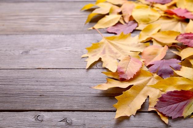 Czerwoni i pomarańczowi jesień liście na drewnianym stole
