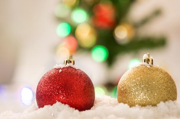 Czerwoni i złociści chrismas balowi na śniegu z chrismas drzewa tłem