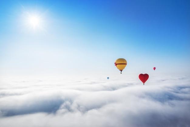 Czerwoni i żółci balony na niebie nad białe chmury i jaskrawe słońce