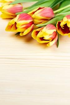 Czerwoni i żółci tulipany na woodentable zbliżeniu, kopii przestrzeń