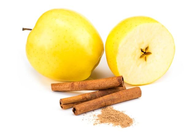 Czerwoni jabłka i cynamonu kije odizolowywający na bielu