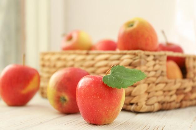 Czerwoni jabłka i łozinowy kosz na drewnianym stole