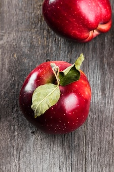 Czerwoni jabłka na ciemnej drewnianej powierzchni