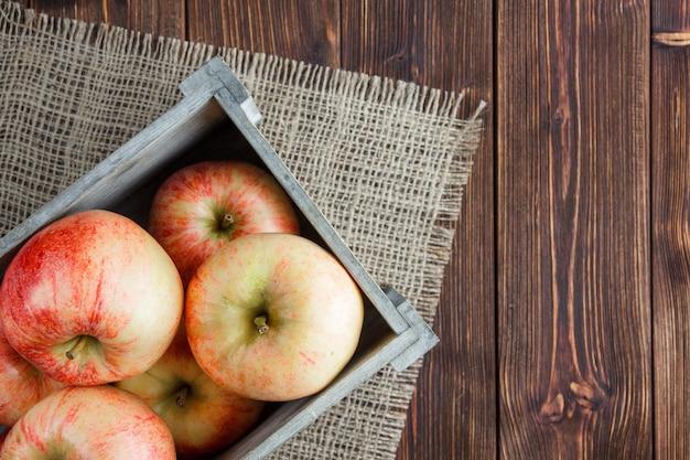 Czerwoni jabłka w drewnianego pudełka odgórnym widoku na parcianej i drewnianej tło przestrzeni dla teksta