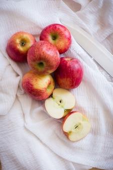 Czerwoni jabłka w drewnianym pucharze na drewnianym tle