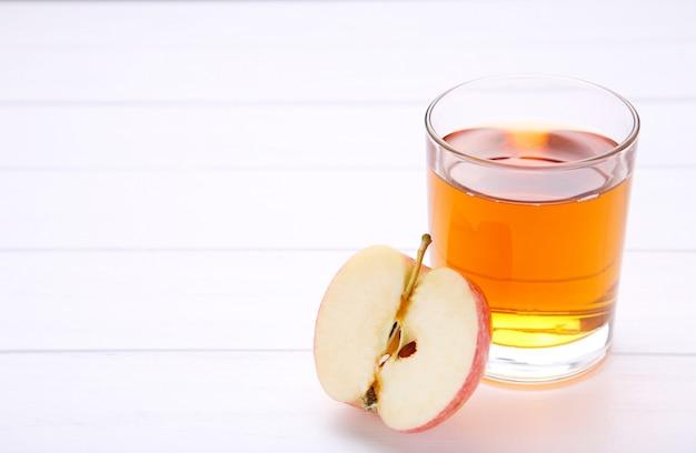 Czerwoni jabłka z sokiem na bielu stole