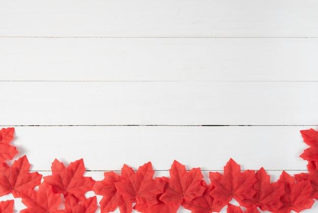 Czerwoni liście klonowi na białym drewnianym tle. jesień, jesień, widok z góry, miejsce.