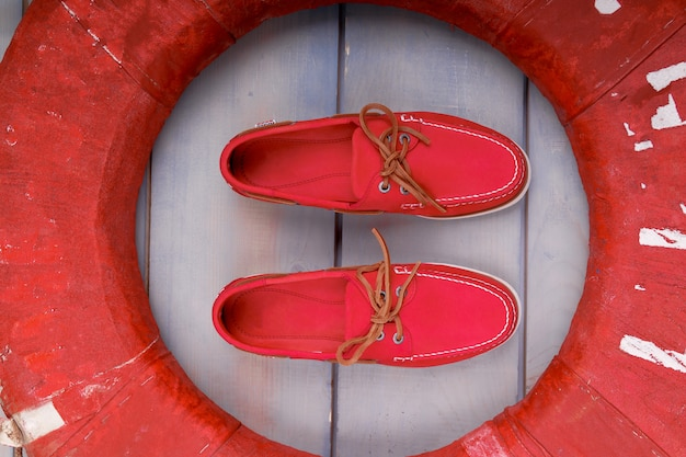 Czerwoni łódź buty na drewnianym tle blisko lifebuoy. widok z góry. ścieśniać.