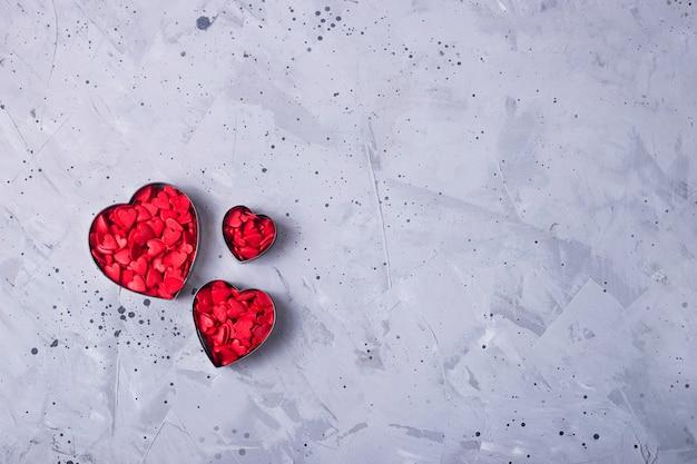 Czerwoni mali serca na popielatym stole jako symbol miłość na walentynka dniu