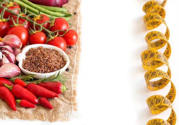 Czerwoni organicznie ryż i surowi warzywa odizolowywający na bielu zakończeniu up