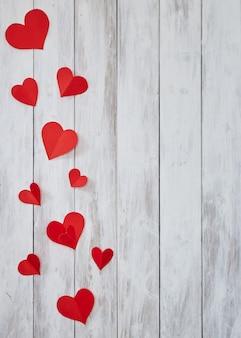 Czerwoni papierowi serca na białym drewnianym stole