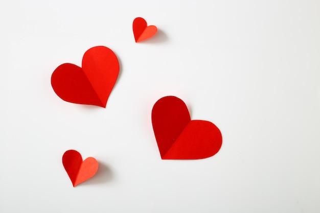 Czerwoni papierowi serca na bielu stole