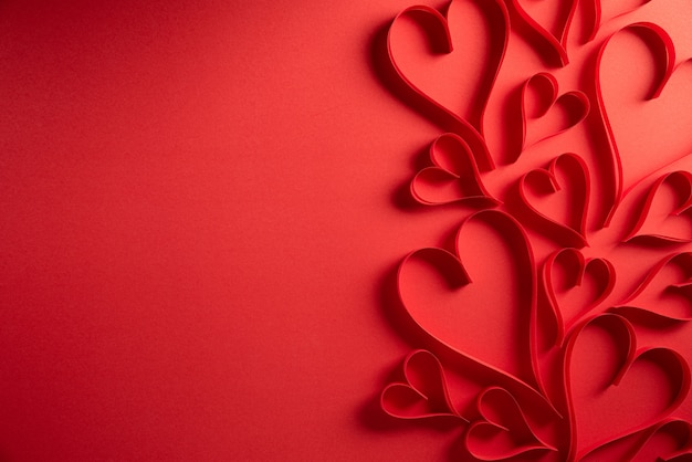 Czerwoni papierowi serca na czerwonym tle. koncepcja miłości i walentynki.