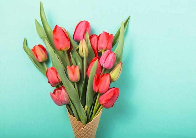 Czerwoni piękni tulipany w lody gofra rożku na koloru błękita tle. koncepcyjny pomysł na prezent kwiatowy. wiosenny nastrój