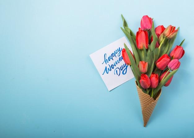 Czerwoni piękni tulipany w lody gofra rożku z karcianym kobieta dniem na betonowym tle. koncepcyjny pomysł na prezent kwiatowy. wiosenny nastrój