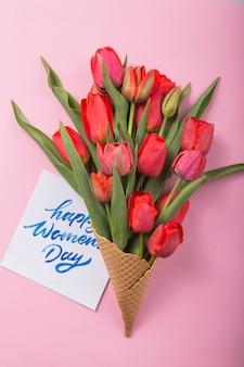 Czerwoni piękni tulipany w lody gofra rożku z kartą na koloru tle. koncepcyjny pomysł na prezent kwiatowy. wiosenny nastrój