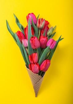 Czerwoni piękni tulipany w lody gofrze konusują koloru tło. koncepcyjny pomysł na prezent kwiatowy. wiosenny nastrój