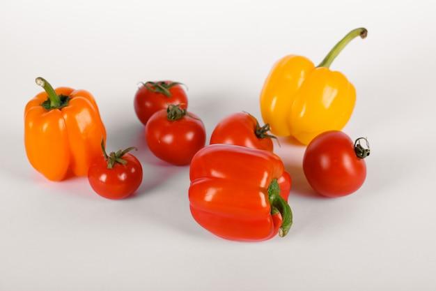 Czerwoni pomidory i papryka na bielu z cieniami. widok z góry