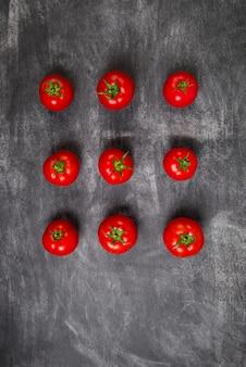 Czerwoni pomidory na drewnianym popielatym stole