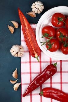 Czerwoni pomidory w białym talerzu na błękitnym backgorund na sprawdzać ręczniku.