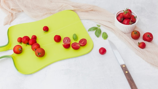 Czerwoni pomidory z basilem na ciapanie desce z nożem i szalikiem na białym tle