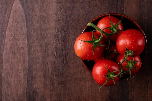 Czerwoni pomidory z kroplami woda w drewnianym talerzu na ciemnym stole