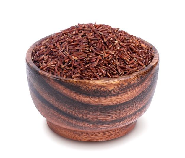 Czerwoni ryżowi groats w drewnianym pucharze odizolowywającym na białym tle