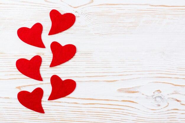 Czerwoni serca filc na białym drewnianym tle