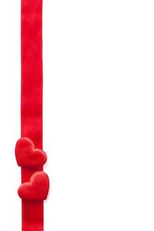 Czerwoni serca i faborku ramowy tło dla walentynek odizolowywać
