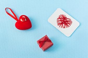 Czerwoni serca i pierścionek na błękitnym tle