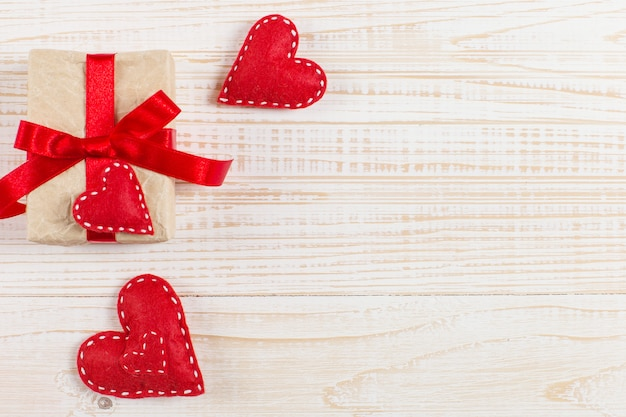 Czerwoni serca i rzemiosło prezenty na białym drewnianym tle
