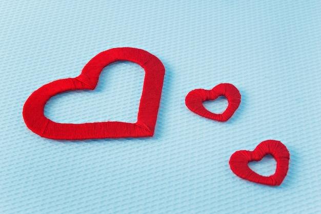 Czerwoni serca na błękitnym tle