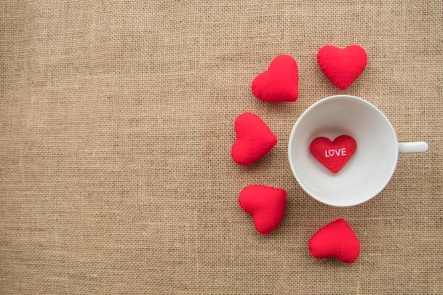 Czerwoni serca round filiżanka w filiżance kawy na workowym tekstury tle i